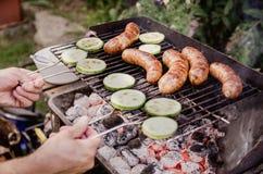 Укомплектуйте личным составом приготовление на гриле в саде овощей и сосисок на гриле Стоковая Фотография