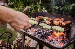 Укомплектуйте личным составом приготовление на гриле в саде овощей и сосисок на гриле Стоковая Фотография RF