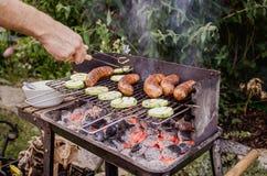 Укомплектуйте личным составом приготовление на гриле в саде овощей и сосисок на гриле Стоковые Изображения