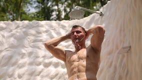 Укомплектуйте личным составом принимать ливень под открытое небо на его ванной комнате бунгала на тропическом острове с ладонями  видеоматериал