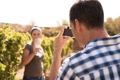 Укомплектуйте личным составом принимать фото женщины в винограднике Стоковая Фотография