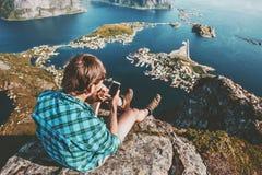 Укомплектуйте личным составом путешественника используя smartphone ослабляя на верхней части горы Стоковое фото RF