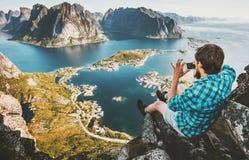 Укомплектуйте личным составом путешественника принимая воздушное фото smartphone сидя на скале Стоковое Изображение RF