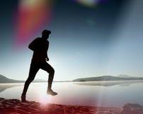 укомплектуйте личным составом работать и протягивать на пляже озера на восходе солнца Здоровый уклад жизни Одна молодая тренировк Стоковые Фотографии RF