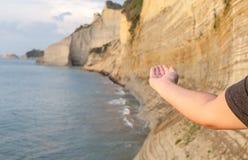 Укомплектуйте личным составом расширять его руку в расплывчатой предпосылке Волны shoaling в взморье Длинные ряды гористой скалы  стоковое изображение