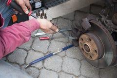 Укомплектуйте личным составом ремонтировать автомобильное отверстие крумциркуль тормоза для изменения Стоковые Фотографии RF