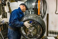 Укомплектуйте личным составом ремонтировать автошину мотоцикла с комплектом для ремонта, комплектом для ремонта штепсельной вилки Стоковое Изображение RF