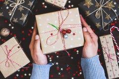Укомплектуйте личным составом руки держа коробку праздничного подарка рождества на украшенной праздничной таблице Стоковая Фотография RF