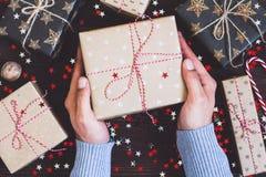 Укомплектуйте личным составом руки держа коробку праздничного подарка рождества на украшенной праздничной таблице Стоковые Фотографии RF