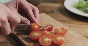 Укомплектуйте личным составом руки отрезая томат вишни на деревянной доске Стоковая Фотография RF