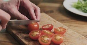 Укомплектуйте личным составом руки отрезая томат вишни на деревянной доске Стоковое Изображение RF
