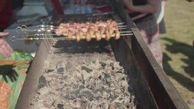 Укомплектуйте личным составом руки ` s делая shashlik и грибы свинины на гриле угля снаружи сток-видео