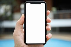 Укомплектуйте личным составом руку держа изолированный телефоном бассейн предпосылки экрана Стоковая Фотография