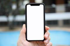 Укомплектуйте личным составом руку держа изолированный телефоном бассейн предпосылки экрана Стоковое Изображение RF