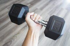 Укомплектуйте личным составом руку держа черную гантель в культуризме спортзала стоковое фото rf
