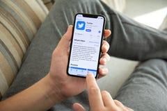 Укомплектуйте личным составом руку держа iPhone x с социальным Twitter обслуживания сети стоковое фото rf