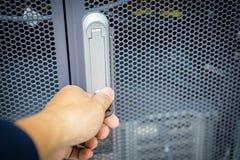 Укомплектуйте личным составом руку на ключевой черной металлической двери шкафа шкафа сервера _ стоковая фотография
