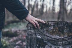 Укомплектуйте личным составом руку на старой надгробной плите предусматриванной с мхом, скорбой и вечной памятью для мертвой конц стоковые фото