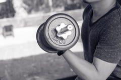 Укомплектуйте личным составом руку поднимая стальную гантель в изображении спортзала мышц остроени черно-белых, жизни и концепции Стоковая Фотография RF