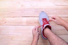 Укомплектуйте личным составом руку связывая шнурки идущих ботинок перед тренировкой на woode стоковые фото