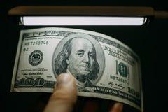 Укомплектуйте личным составом руку с стогом 100 долларов США счетов над банкнотой Стоковые Фото