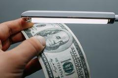 Укомплектуйте личным составом руку с стогом 100 долларов США счетов над лампой, Стоковые Фотографии RF