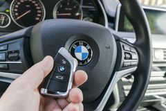 Укомплектуйте личным составом руку ` s держа беспроволочный ключ автомобиля BMW X5 F15 в черном кожаном интерьере современные дет Стоковое Изображение