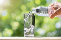 Укомплектуйте личным составом руку ` s держа воду бутылки питьевой воды и лить воду в стекло на деревянной столешнице на запачкан Стоковые Фотографии RF