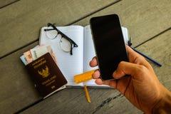 Укомплектуйте личным составом руку ` s используя экран черноты мобильного телефона Стоковая Фотография