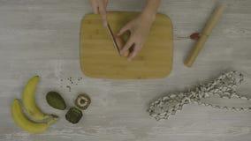 Укомплектуйте личным составом руку ` s на деревянной доске при нож режа сосиску На таблице много ножницы, нож, видеоматериал