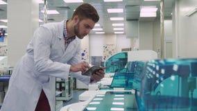 Укомплектуйте личным составом сальто на таблетке около машины лаборатории стоковое изображение