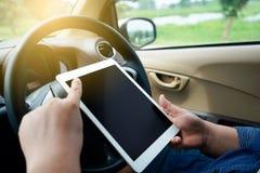 Укомплектуйте личным составом сидеть в автомобиле, держа таблетку касания стоковое изображение
