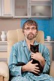 Укомплектуйте личным составом сидеть в стуле с котенком Стоковые Фото