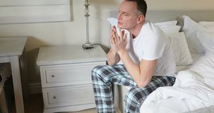 Укомплектуйте личным составом сидеть на кровати после просыпать вверх в спальне 4k сток-видео