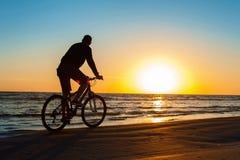 Укомплектуйте личным составом силуэт велосипедиста на голубом небе и пестротканом backg захода солнца Стоковые Изображения