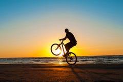 Укомплектуйте личным составом силуэт велосипедиста на голубом небе и пестротканом backg захода солнца Стоковое фото RF