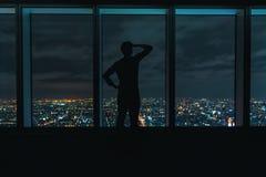 Укомплектуйте личным составом смотреть вне большие окна высокие над разваливаясь городом Стоковые Фотографии RF