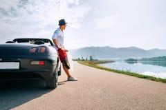 Укомплектуйте личным составом сольного путешественника на остатках автомобиля cabriolet на живописной горе Стоковое Изображение