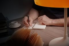 Укомплектуйте личным составом сочинительство в тетради на деревянном столе стоковые фотографии rf