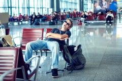 Укомплектуйте личным составом спать пока сидящ в крупном аэропорте и ждать f стоковые изображения