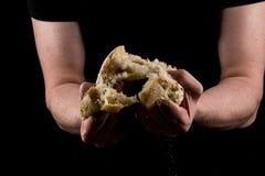 Укомплектуйте личным составом срывать часть в середине хлеба для того чтобы делить Концепция рук помощи делить Стоковые Фото