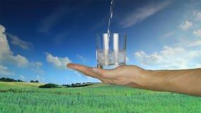 Укомплектуйте личным составом стекло владением руки и полейте свежую воду от бутылки в стекло на предпосылке ландшафта природы видеоматериал