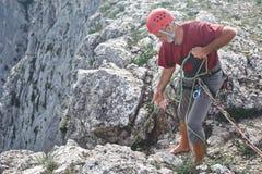 Укомплектуйте личным составом стойки альпиниста утеса на верхней части скалы и belays партнер Стоковые Изображения RF