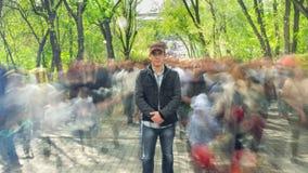 Укомплектуйте личным составом стоящее самостоятельно в запачканной толпе, на деревьях зеленого цвета предпосылки Камера причалива сток-видео