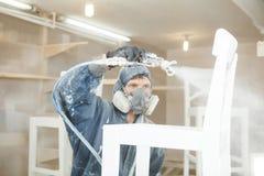 Укомплектуйте личным составом стул картины в белую краску в дыхательной маске Применение пламени - retardant обеспечивающ защиту  стоковые фото