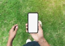 Укомплектуйте личным составом телефон владением показывая пустой экран идя на лужайку стоковая фотография rf