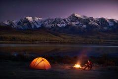 Укомплектуйте личным составом туристов сидя в загоренном шатре около лагерного костера Стоковая Фотография RF