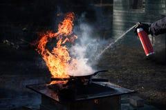 Укомплектуйте личным составом тушить огонь на железном лотке с пеной от брызга Стоковые Изображения RF