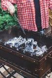 Укомплектуйте личным составом угли граблей в меднике с покером металла стоковое фото rf