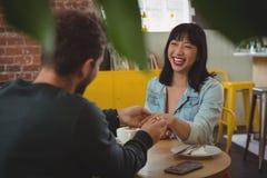 Укомплектуйте личным составом установку кольца на палец женщины на кафе Стоковые Изображения